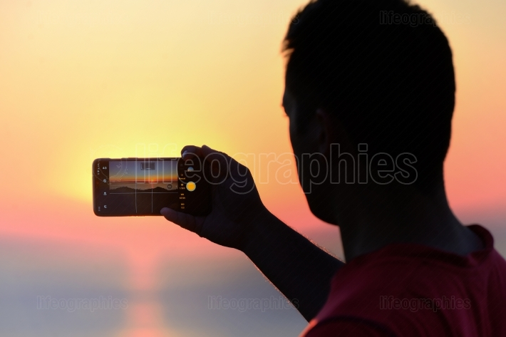 Taking photo at sunset with smartphone