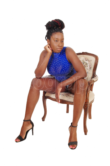 Tall African American woman sitting sin shorts in a armchair