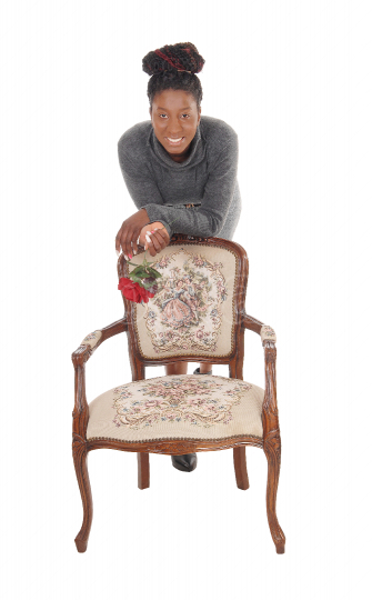 Tall gorgeous African woman standing behind an old chair