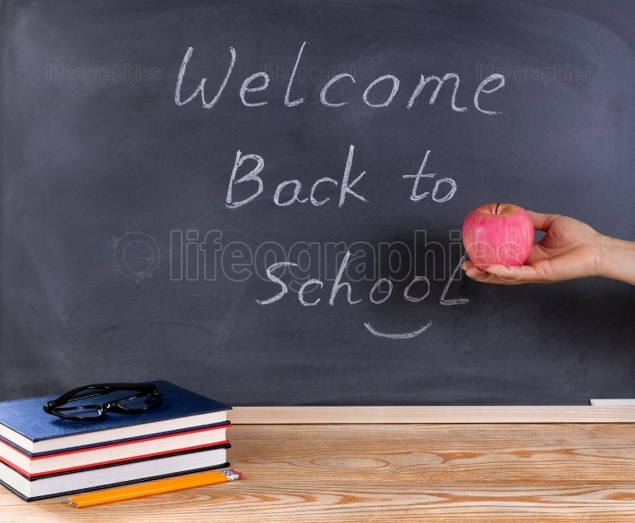Teacher holding red apple in front of chalkboard with welcome ba