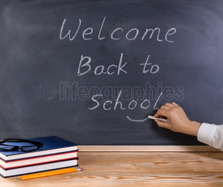 Teacher placing smile symbol on welcome back to school message w
