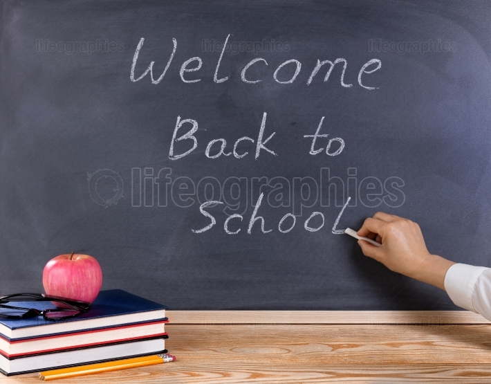 Teacher writing welcome back to school on erased black chalkboar