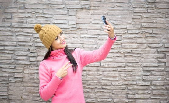 Technology internet and happiness concept. Woman happy girl taking self picture selfie with smartphone camera outdoors
