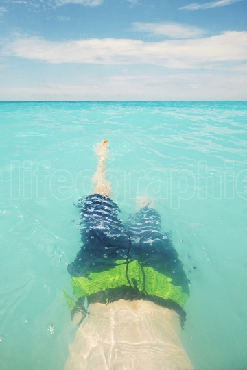 Teen boy swimming in turquoise water