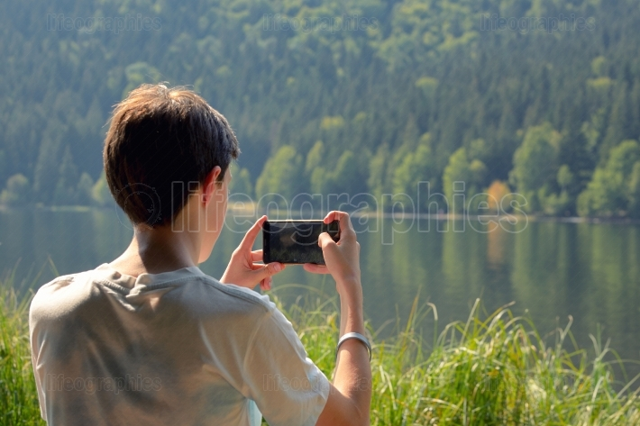 Teen boy taking picture with smartphone