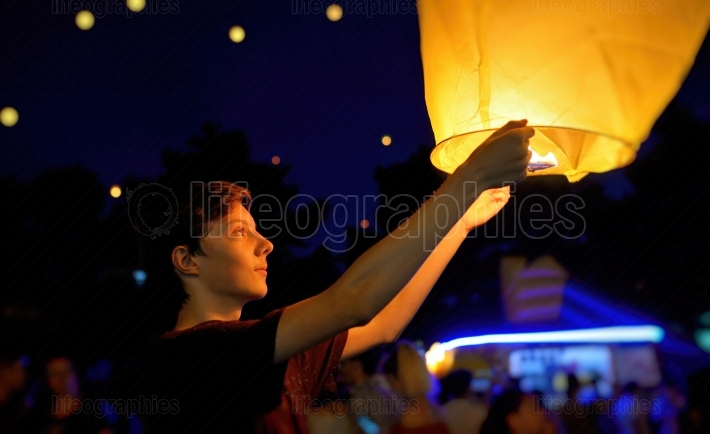 Teen boy with paper flying lanterns