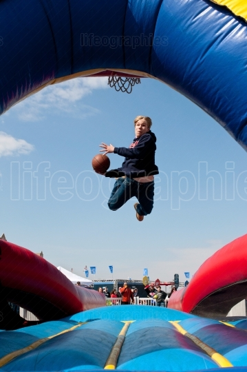 Teen Gets Airborne Attempting To Dunk Basketball In Carnival Gam