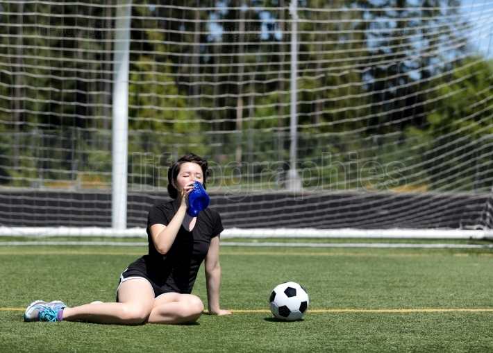 Teen girl drinking a lot of water during a hot day on the soccer