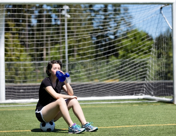 Teen girl drinking water while sitting on soccer ball