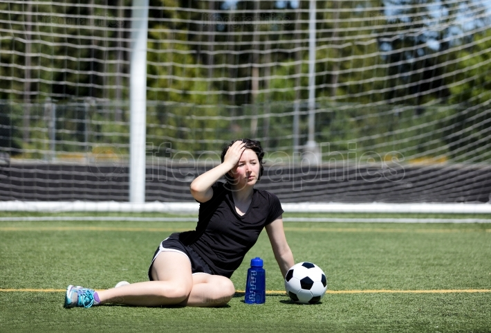 Teen girl feeling too hot on soccer field on hot day