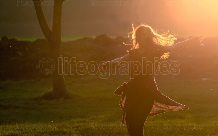 Teen girl jump against beautiful sunset