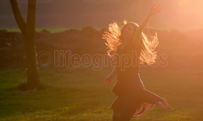 Teen girl jump against sunset in forest