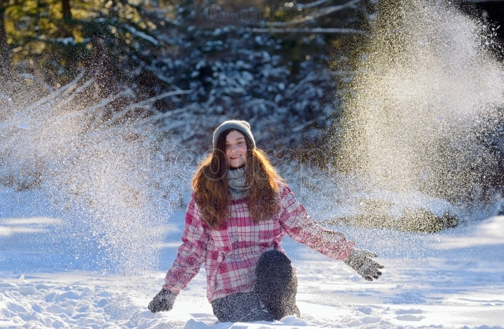 Teen girl playing in snow