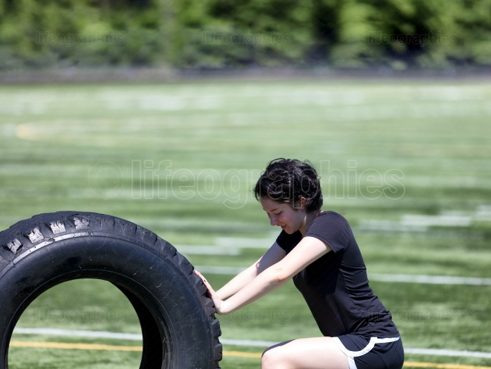 Teen girl pushing heavy old tire on sports field during hot day