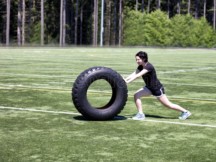 Teen girl pushing heavy tire on sports field during hot day