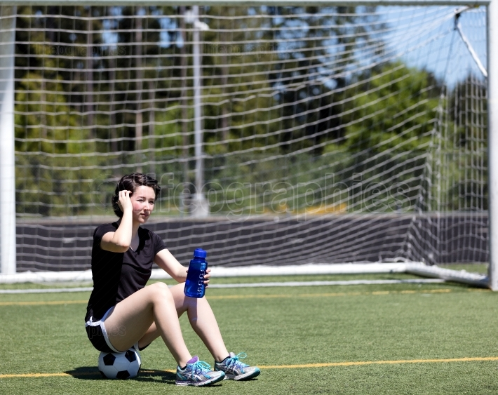 Teen girl resting on soccer ball while holding water bottle