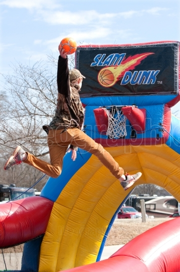 Teen Soars Above Rim To Dunk Basketball In Carnival Game
