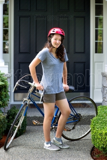 Teenage girl outdoors resting on her bicycle while in front of h