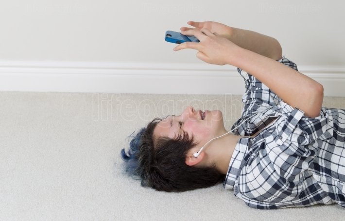 Teenage girl relaxing while on her cell phone and listening to m