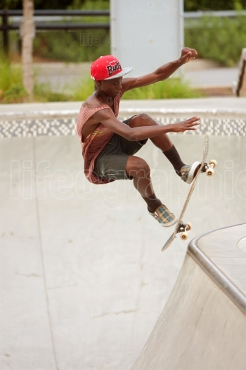 Teenager Performs Jump While Practicing Skateboarding At Skatebo