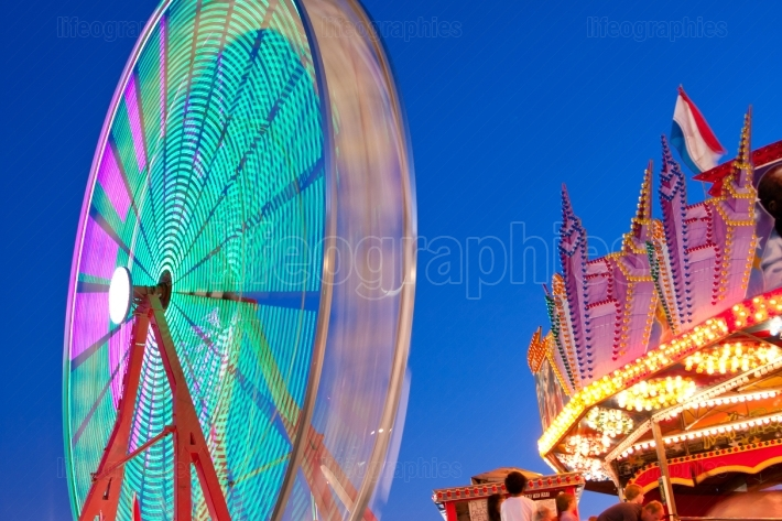 The Circular Motion Of A Ferris Wheel Blurs At Twilight