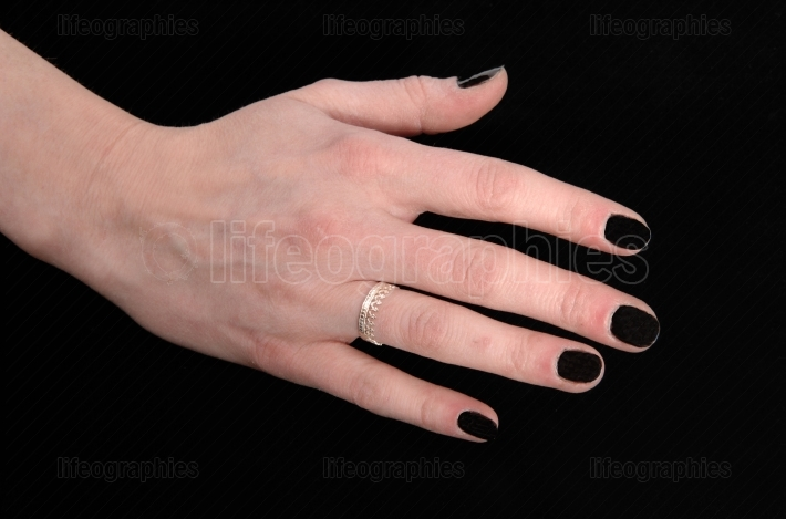 The hand of a woman on black background
