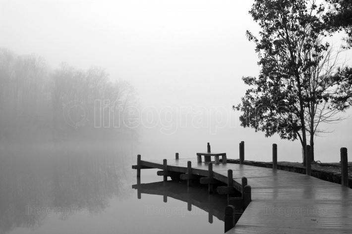 Thick blanket of fog covers lake and wooden dock