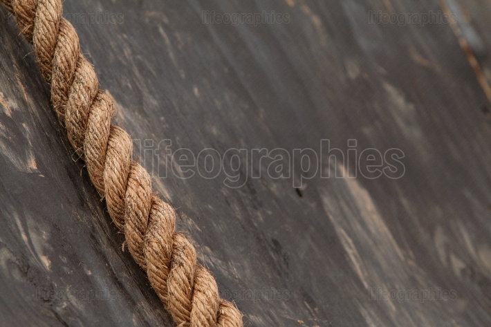 Thick rope lies against wooden wall at extreme obstacle course