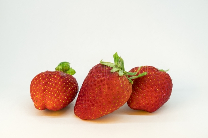 Three perfectly cleaned strawberries with leaves isolated on the