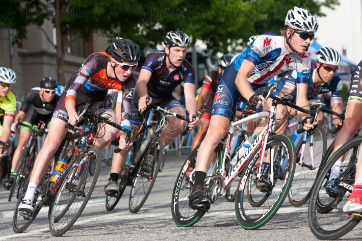 Tight pack of cyclists lean into turn in amateur race