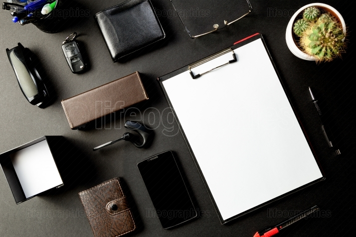 Top view of office desk with mock up paper, eyeglass, pen, smart