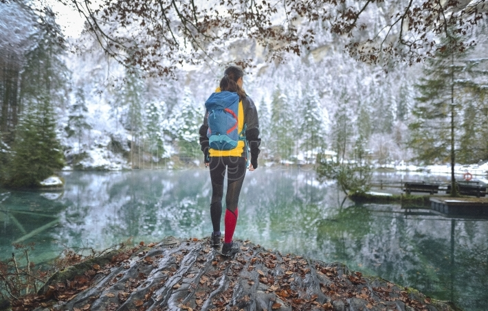Tourist hiker on cold weather admire a lake from Blausee. Switzerland