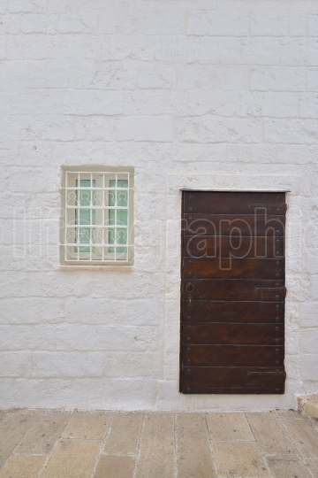 Traditional facade of south adriatic sea house with door and window minimalist decorated in small village of Monopoli, south Italy