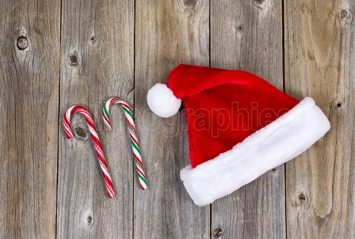 Traditional holiday Santa Claus cap and candy canes on rustic wo