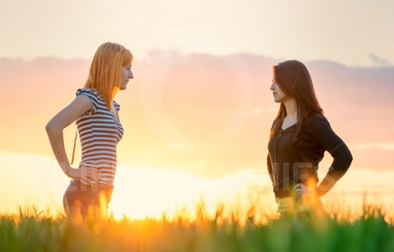 Two beautiful girl in the sunset having an argue