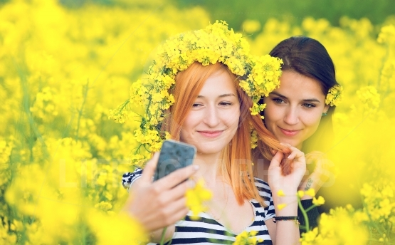 Two friends taking a selfie in a field with  yellow flowers of rapeseed