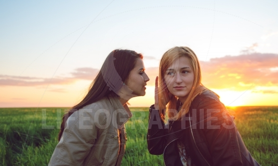 Two girl friends whispering secrets