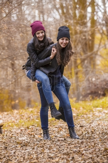 Two girls having fun in autumn park
