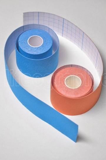Two kinesio tape rolling arranged in tao shape