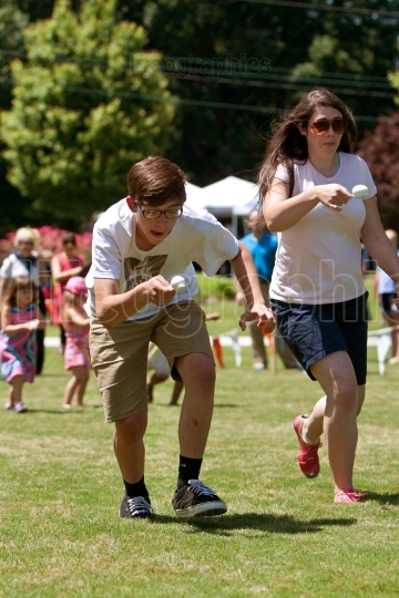 Two People Run In Egg and Spoon Race At Festival