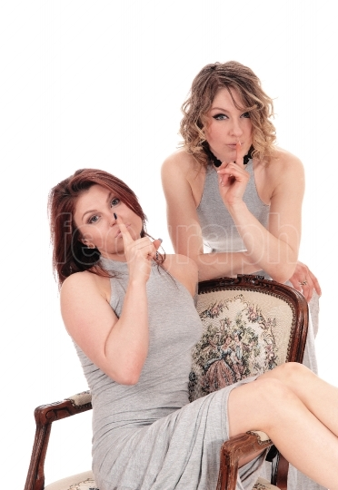 Two woman with finger over mouth