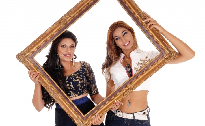 Two women holding picture frame.