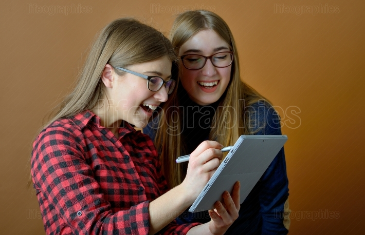 Two young girls using pc tablet