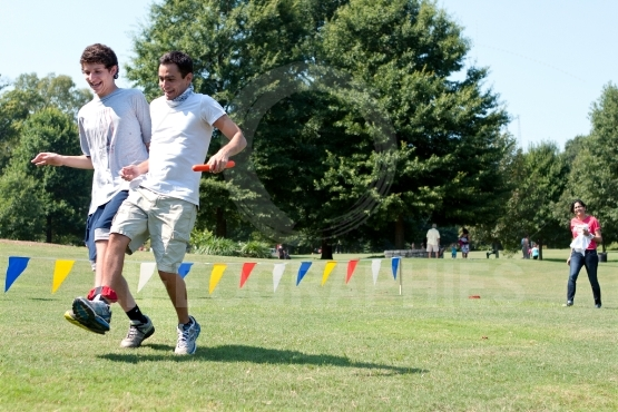 Two Young Men Compete In Three Legged Race At Summer Fundraiser