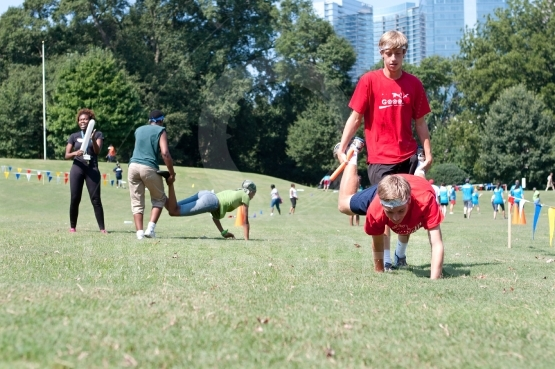 Two Young Men Compete In Wheelbarrow Race At Summer Fundraiser