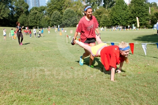 Two Young Women Compete In Wheelbarrow Race At Summer Fundraiser