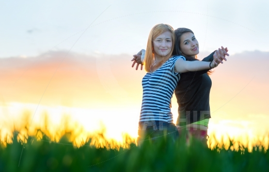 Two young women hugging and rest in the rays of sunset outdoors. Best friends