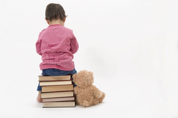 Upset child sitting on books with her teddybear