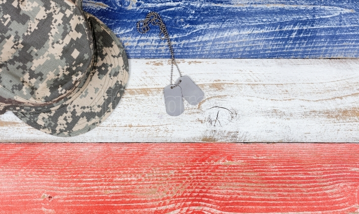 USA national colors with military cap and ID tags on wooden plan