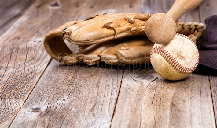 Used baseball equipment on rustic wooden boards